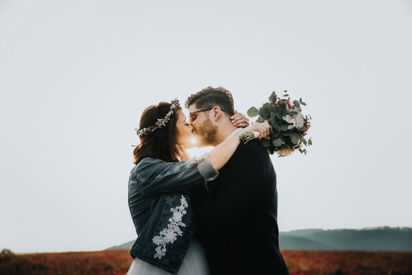 Married couple kissing during sunrise